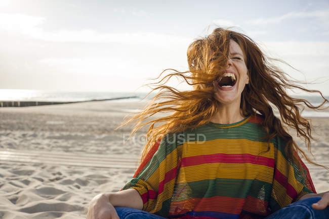 Mulher que senta-se na praia, gritando para a alegria — Fotografia de Stock