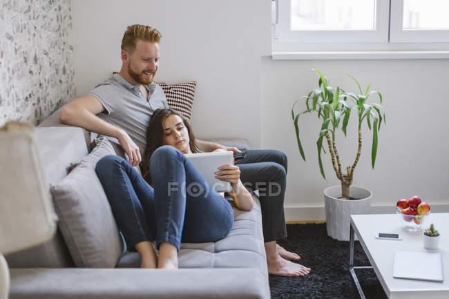 Пара на дивані у вітальні за допомогою планшета. — стокове фото