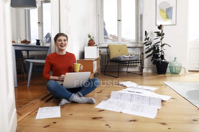 Frau sitzt querbeinig auf dem Boden ihres Hauses, mit Laptop — Stockfoto