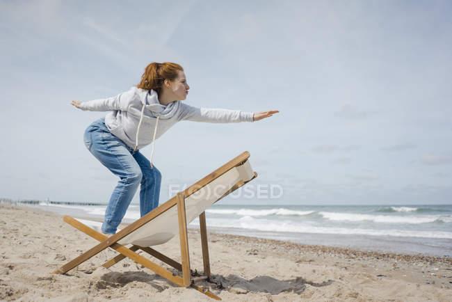 Femme restant sur la présidence de plate-forme, faisant semblant de surfer — Photo de stock