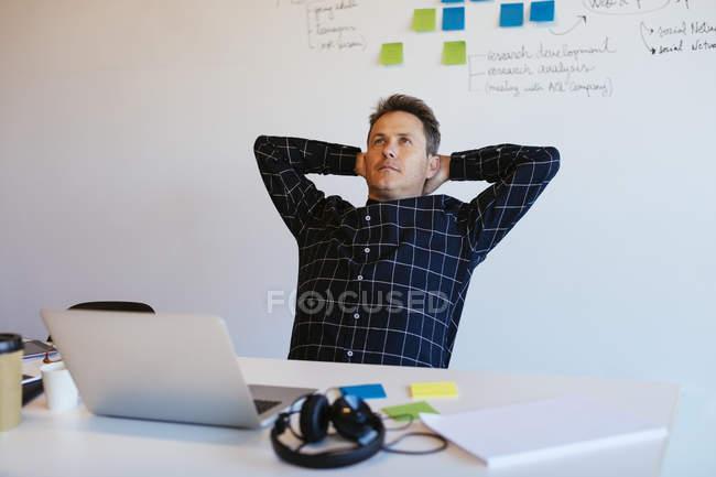 Uomo d'affari appoggiato alla scrivania in ufficio — Foto stock
