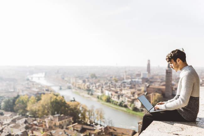 Italia, Verona, turista utilizando ordenador portátil en el punto de observación - foto de stock