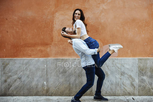 Carefree couple in love in front of a wall outdoors — Stock Photo