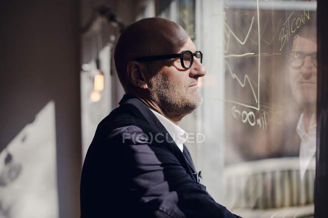 Brainstorming aîné d'homme d'affaires, dessinant des formules sur la vitre — Photo de stock