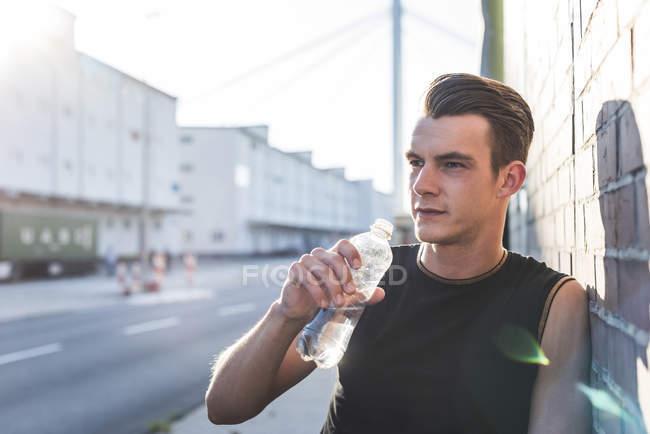 Alemania, Mannheim, Joven atleta en la ciudad con botella de agua, retrato - foto de stock