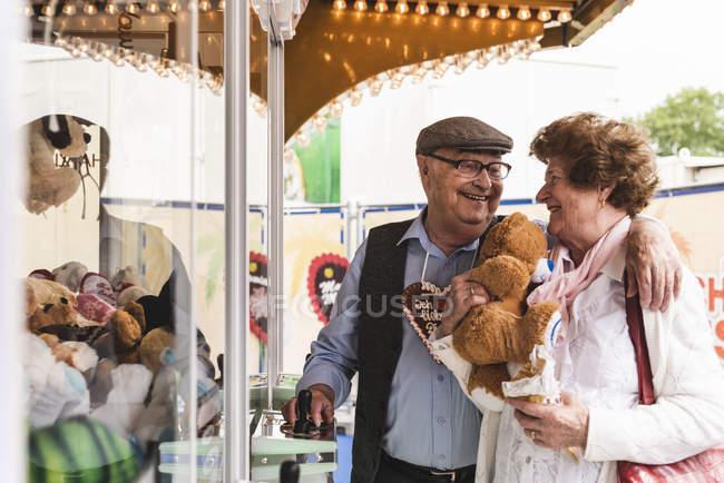 Casal sênior feliz com prêmio na feira — Fotografia de Stock