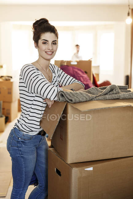 Young woman moving house, unpacking cardboard boxes — Stock Photo