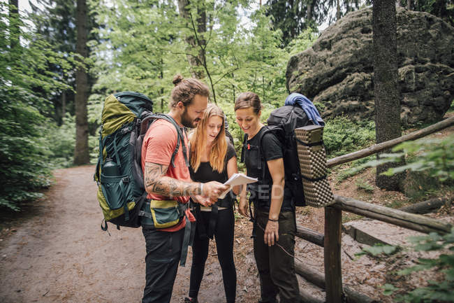 Friends on a hiking trip reading map — Stock Photo
