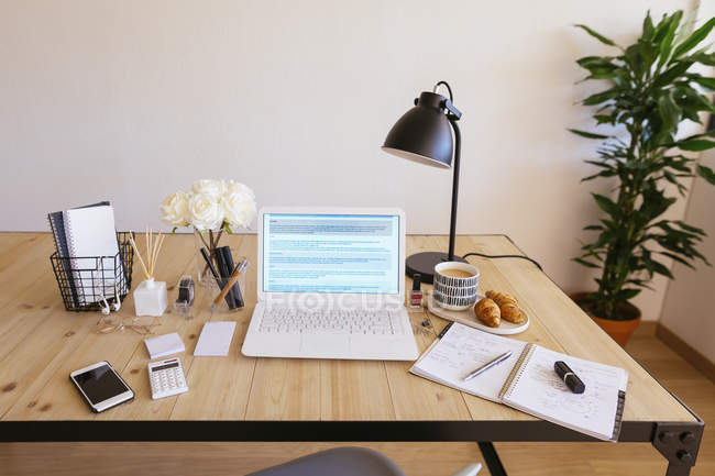 Laptop on desk in a bright and friendly office — Stock Photo