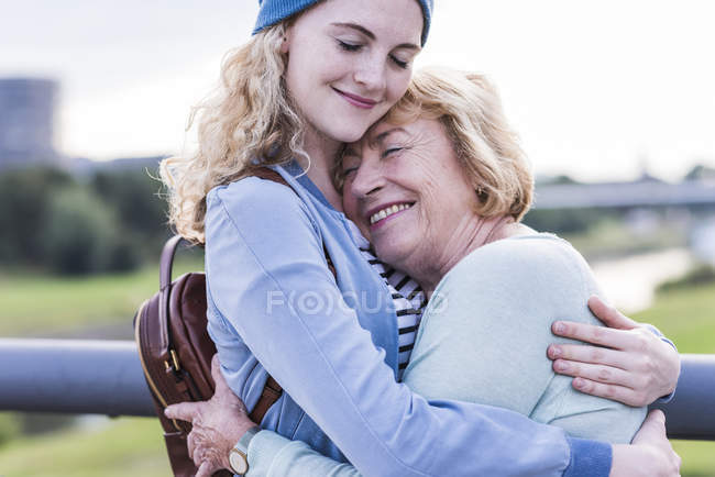 Happy grandmother and granddaughter hugging each other — Stock Photo