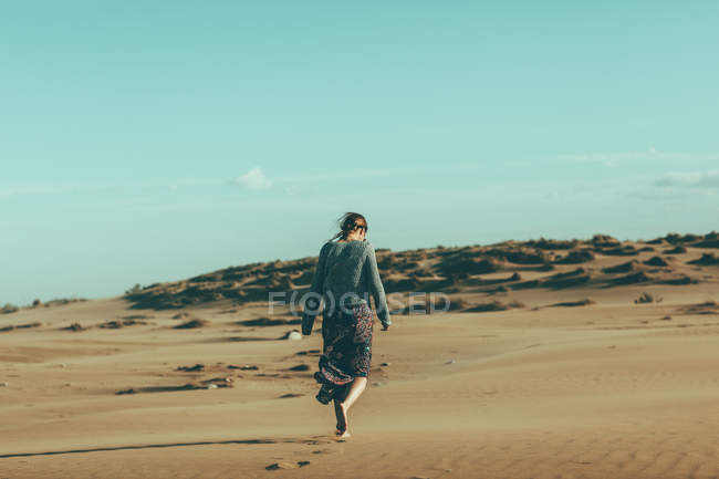 Young woman walking in desert landscape — Stock Photo