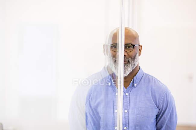 Porträt eines kahlen afrikanischen amerikanischen Geschäftsmannes und sein Spiegelbild auf Glasscheibe — Stockfoto