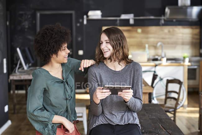 Dos mujeres jóvenes riendo con la tableta en la oficina - foto de stock