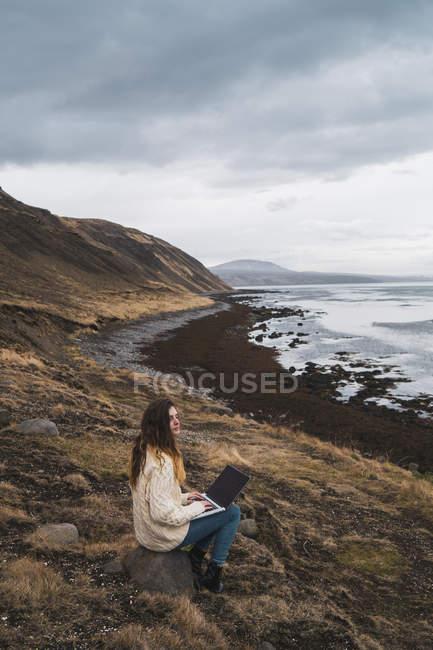 Исландия, женщина с ноутбуком на берегу — стоковое фото