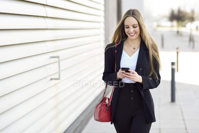 Portrait of content businesswoman using cell phone — Stockfoto