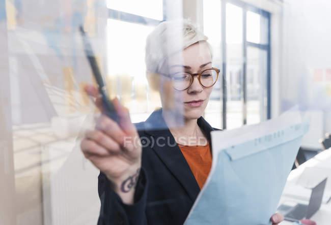 Empresária que trabalha em documento no escritório — Fotografia de Stock