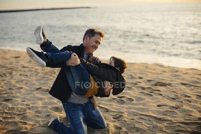Father and son playing on beach — Stock Photo