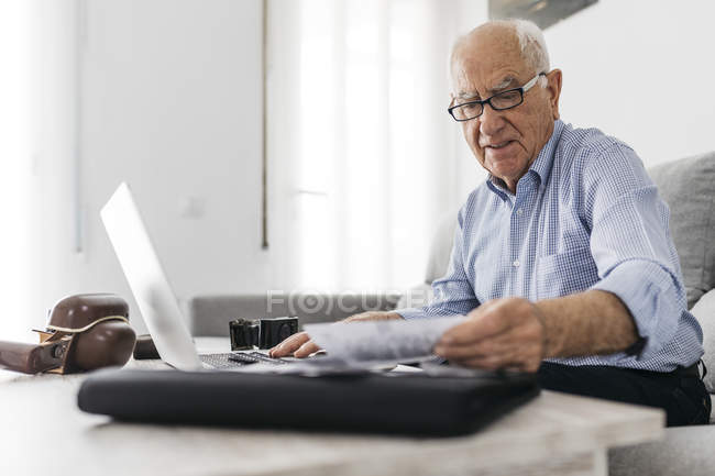 Senior man working with a computer and his old photo cameras and old photos — Stock Photo