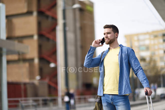 Young man with smartphone at station — Stock Photo