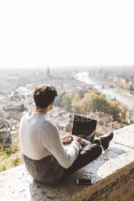 Італія, Верона, задній погляд туриста використання ноутбука в точці спостереження — стокове фото