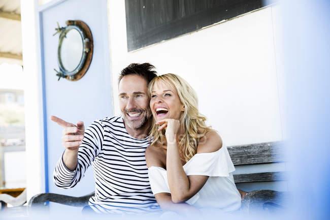Couples heureux s'asseyant sur la plage découvrant quelque chose — Photo de stock