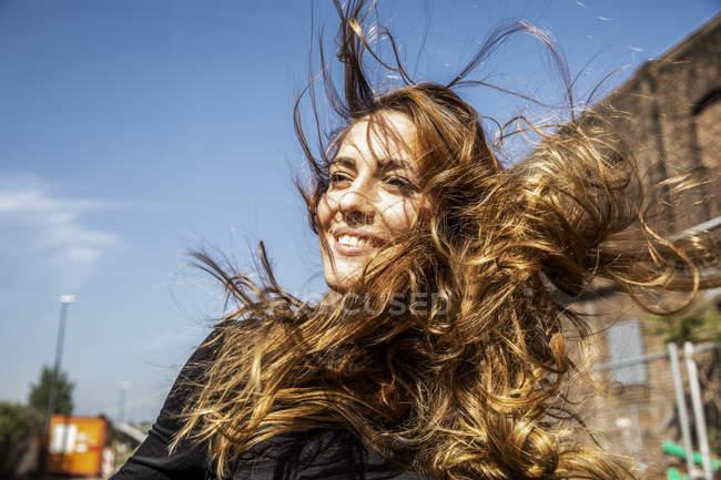 Портрет усміхається жінка задувною волосся — стокове фото