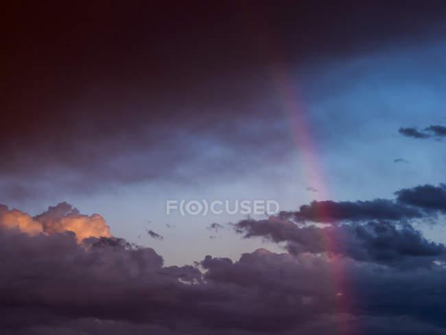 Austria, Hoersching, dark clouds after thunderstorm and rainbow — Stockfoto