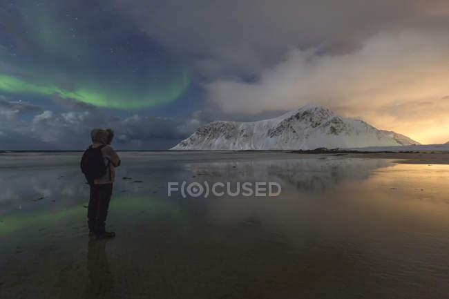 Norvège, Lofoten, Vareid, Flakstad, homme observant le coucher du soleil et les aurores boréales — Photo de stock
