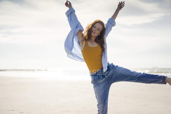 Femme heureuse s'amuser à la plage, sauter dans les airs — Photo de stock