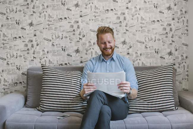 Lächelnder Geschäftsmann liest Zeitung auf Couch im Wohnzimmer — Stockfoto