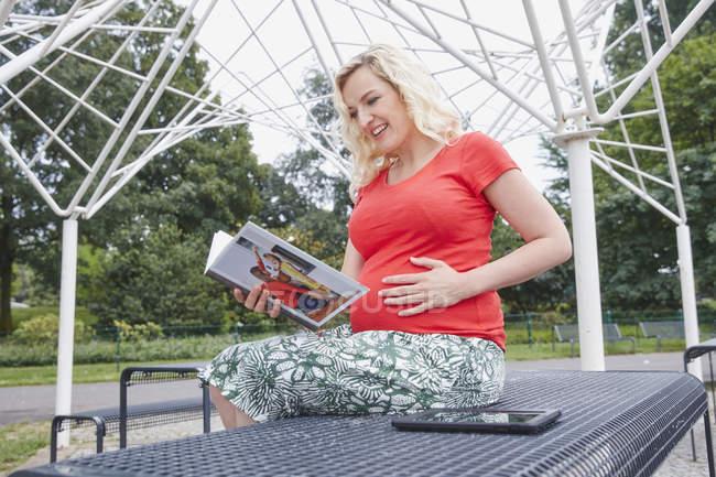 Улыбающаяся беременная женщина сидит в парке и смотрит фотоальбом — стоковое фото