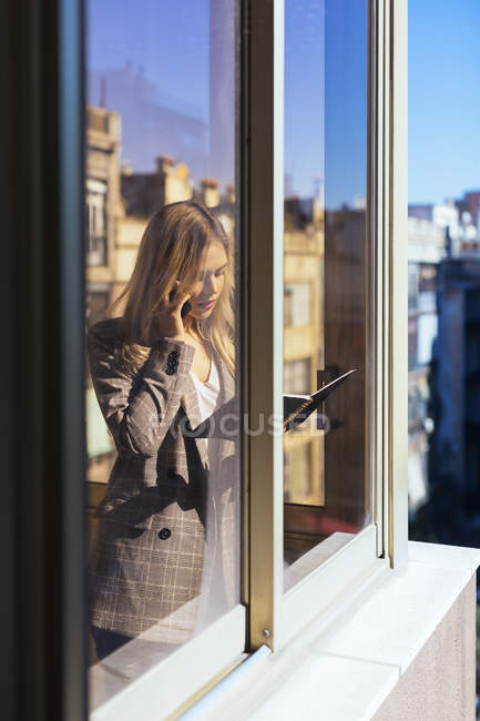 Young businesswoman standing at the window, talking on the phone — Stock Photo