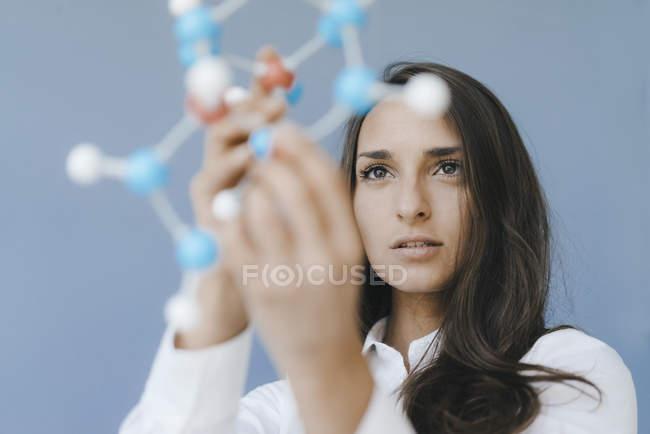 Wissenschaftlerin mit Molekülmodell auf der Suche nach Lösungen — Stockfoto