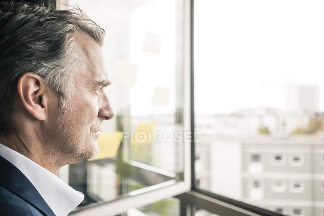 Серьезный зрелый бизнесмен, выглядывающий в окно — стоковое фото