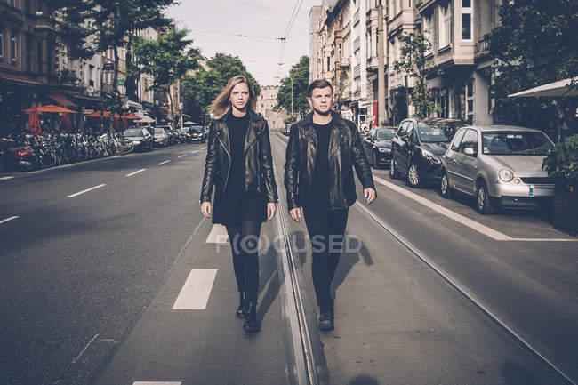 Casal jovem vestindo roupas combinando preto andando lado a lado na rua — Fotografia de Stock