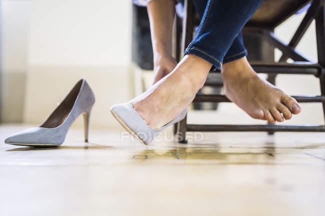 Imagem cortada de Empresária sentado e decolando saltos altos — Fotografia de Stock