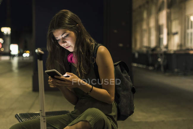 Young woman with backpack and baggage using cell phone at night — Stock Photo