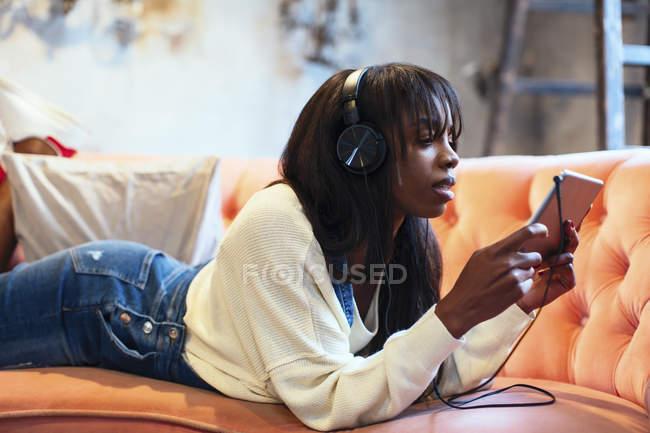 Jeune femme couchée sur le canapé en utilisant une tablette et un casque — Photo de stock
