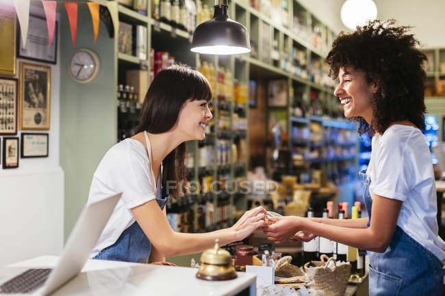 Deux femmes heureuses au comptoir dans un magasin — Photo de stock