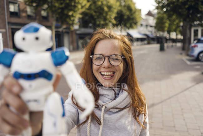 Mujer pelirroja que muestra robot de juguete - foto de stock