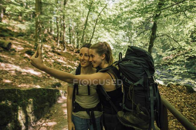 Дві молоді жінки подорожують автостопом і роблять селфі. — стокове фото