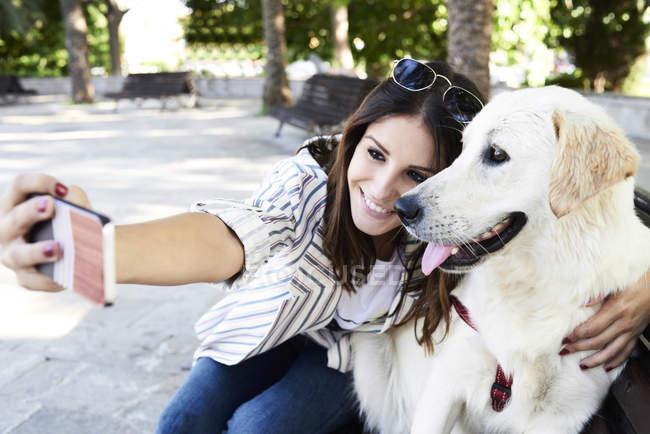 Joyeux jeune femme prenant selfie avec son chien — Photo de stock