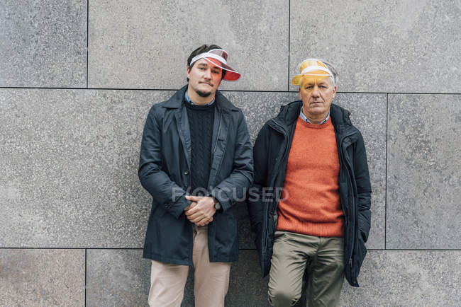 Portrait of young man and senior man wearing sun visors leaning against a wall — Stock Photo