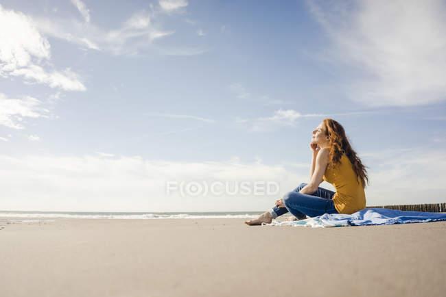 Woman sitting on the beach, enjoying the sun — Stock Photo