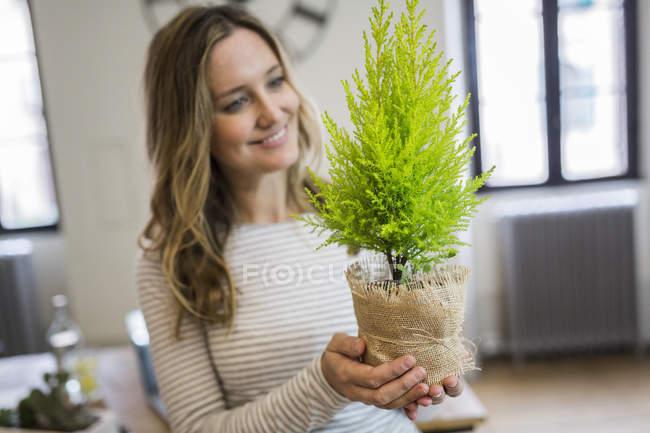 Lächelnde Frau hält Pflanze zu Hause — Stockfoto