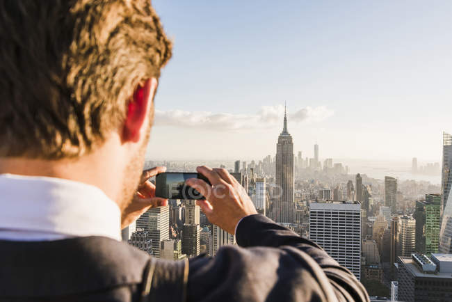 USA, New York City, man taking cell phone picture on Rockefeller Center observation deck — Stock Photo