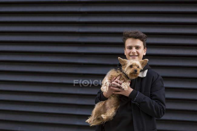 Портрет улыбающегося подростка со своей собакой на черном фоне — стоковое фото