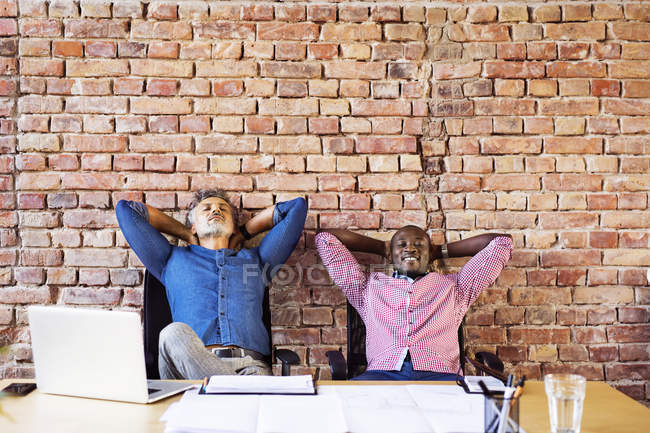 Wo colleagues sitting relaxed in office, taking a break - foto de stock