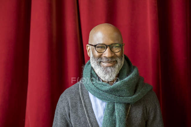Portrait of smiling african american man wearing glasses and scarf in front of red curtain — Stock Photo