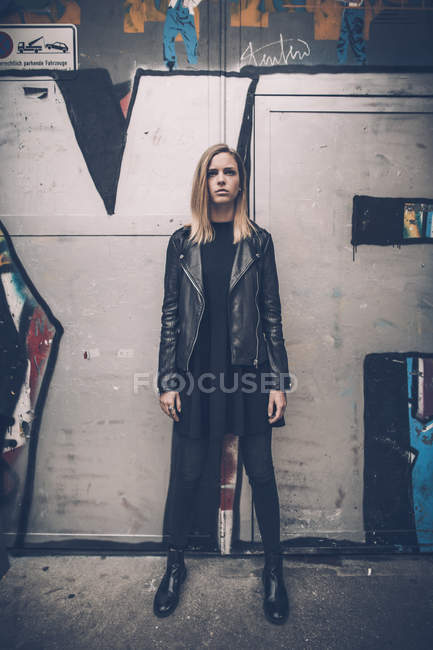 Ritratto di giovane donna seria vestita di nero in piedi davanti a graffiti — Foto stock
